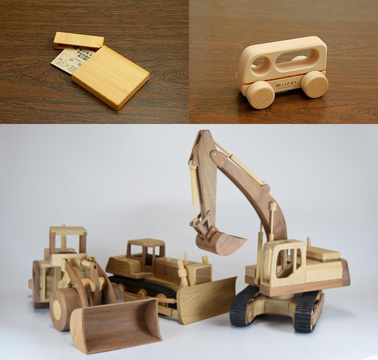 左上はイチイ製の名刺ケース。ほかにもスマホケースなど、実用的な小物は多数揃っています。右上は「milcar」シリーズのグリップカー。下はブルドーザーなど3台の重機。